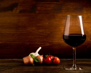 photo of delicious red wine goblet with fresh ingredients on wooden table